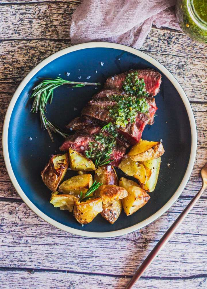chimichurri served over slices of churrasco steak and potatoes