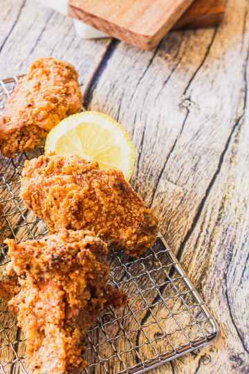 a shot showing the crispy texture of the fried crust on lemon pepper chicken wings on a metal wire rack