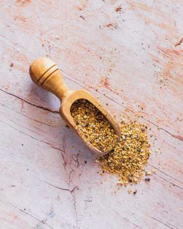 a spice shovel spills lemon pepper seasoning onto a wood table