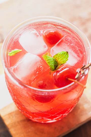 overhead view of a shirley temple with ice, cherries, and a sprig of mint