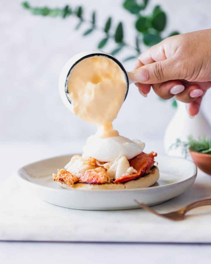 hollandaise sauce being poured onto lobster benedict
