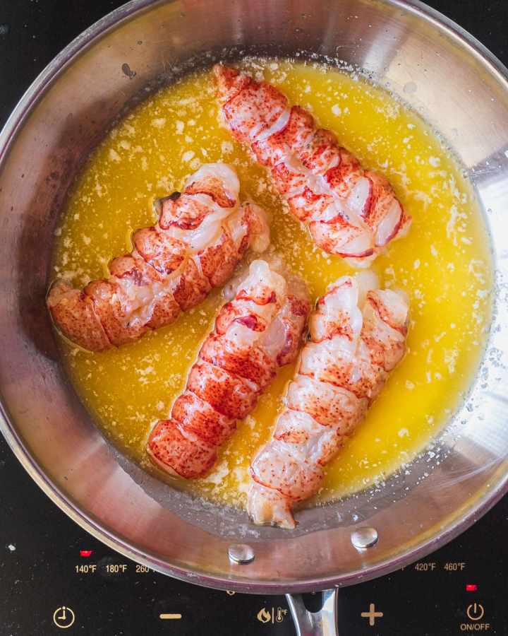 lobster tails being poached in unsalted butter in a pan