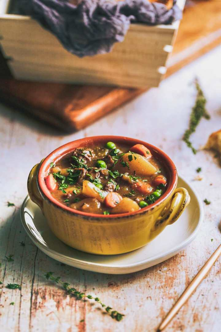 a close view of a bowl of beef stew full of potatoes, carrots, peas, and beef dusted with parsley