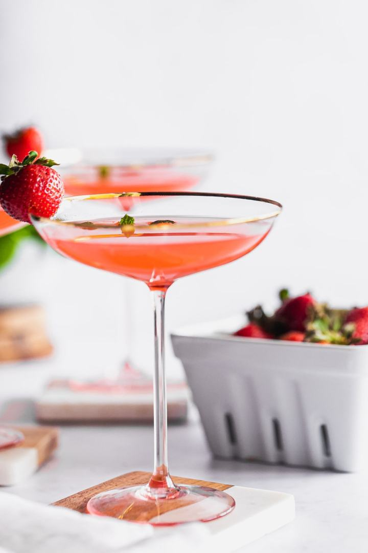 side view of southern flamingo cocktail in anthropologie gilded rim coupe, garnished with a strawberry