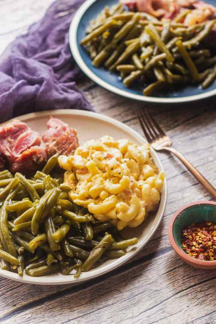 two plates of old fashioned southern green beans with ham hock and  southern baked mac and cheese