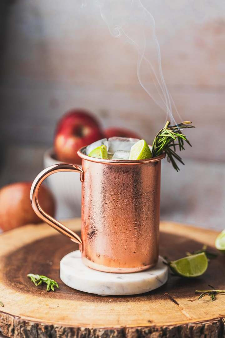 a profile shot of a chilled copper cup full of apple cider mule with limes and a smoking rosemary sprig for garnish