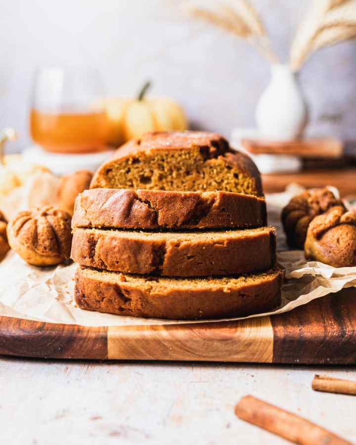 a front shot of slices of pumpkin bread cut from the loaf of bread surrounded by cakelets