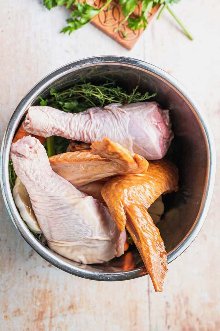 overhead view of roasted turkey wings and fresh turkey legs in the instant pot with mirepoix and herbs to make turkey stock