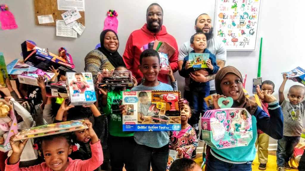 -Councilman Kenyatta Johnson with some very happy youngsters at his annual Christmas toy give-away on December 23rd.