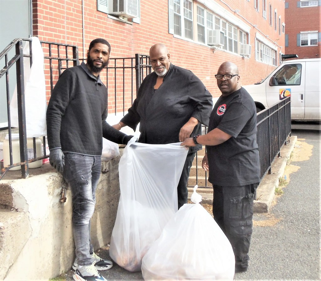 Chef Ricky Hill (Center) and his team at the Outley House Men's Shelter Team bag up bagels which had been collected Friday morning from bakeries along the suburban mainline by members of the Men's Fellowship at Wayne Presbyterian.