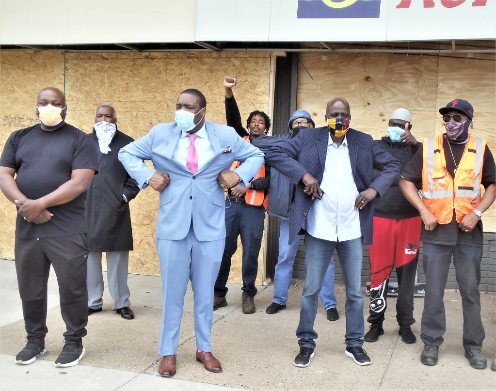 Establishing some social distance,  Councilman Kenyatta Johnson (2nd from left) and ACANA founder and CEO Voffee Jabateh (next at right) gathered with civic leaders in front of boarded-up stores amid the wreckage of looting at the Woodland Plaza Shopping Center June 2.