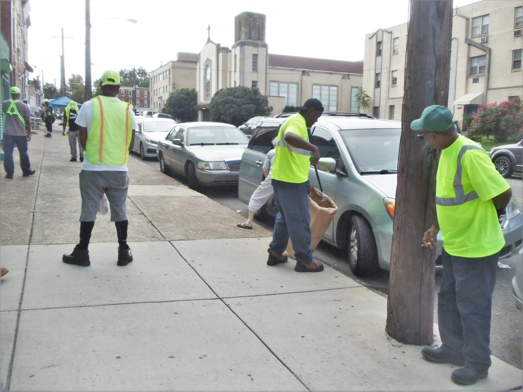 Streets department employees unable to perform their normal duties have recently been assigned to cleanup teams on busy commercial corridors.  Shown here, properly masked and distanced,  at the 71st Street corner are members of a 45-person group working to clean up Woodland Avenue.