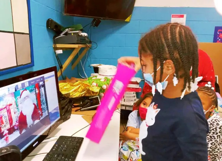 A child opens her gift while talking to Santa at one of the City's Access Centers in Southwest.