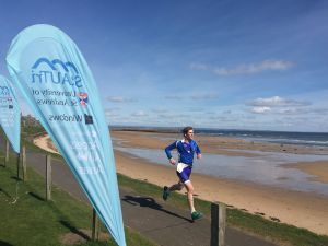 Striding towards a beachside finish line at St Andrews Sprint Triathlon