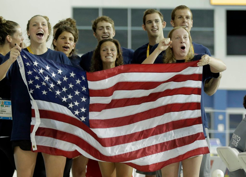 Jul 17, 2015; Toronto, Ontario, CAN; United States swim team members wave a flag during the medal ceremony for the women's swimming 400m individual medley final the 2015 Pan Am Games at Pan Am Aquatics UTS Centre and Field House. Mandatory Credit: Erich Schlegel-USA TODAY Sports
