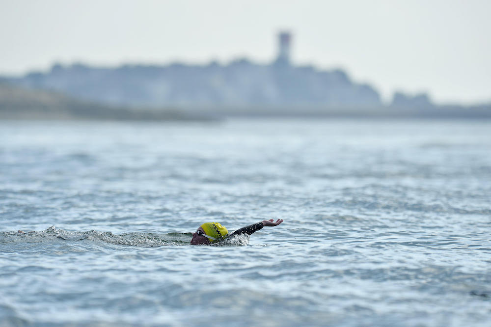 A swimmer does the backstroke with the town of Winthrop in the distance during the 2018 Swim Across America Boston Harbor open water swim on Friday July 13, 2018. Photo by Joseph Salvatore Prezioso