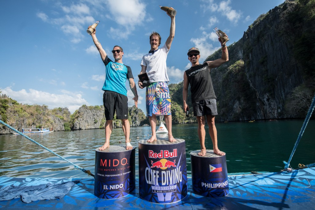 Constantin Popovici of Romania, Gary Hunt of the UK and Jonathan Paredes of Mexico celebrate on the podium at the Big Lagoon on Miniloc Island during the final competition day of the first stop of the Red Bull Cliff Diving World Series in Palawan, Philippines on April 13, 2019. // Romina Amato/Red Bull Content Pool // AP-1Z15215ZH1W11 // Usage for editorial use only // Please go to www.redbullcontentpool.com for further information. //