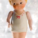 Nippon all-bisque, girl bather doll, with jointed arms, in a pink. ribbon-trimmed sun suit