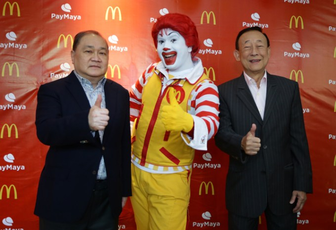 PLDT, Smart, Voyager and PayMaya Chairman Manuel V. Pangilinan (left) and McDonald's Philippines Founder and Chairman George T. Yang (right) give a thumbs up to building a cashless ecosystem in the Philippines along with McDonald's Chief Happiness Officer Ronald McDonald (middle). Starting today, Filipinos can pay for their favorite McDonald's treats at select stores nationwide using any Visa or Mastercard credit, debit, or prepaid card, with QR codes for select McCafe stores and online card payments for McCelebrations birthday party reservations and McDelivery coming very soon.