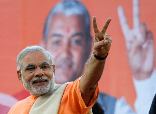 Narendra Modi, chief minister of Gujarat state, gestures on the podium during a felicitation ceremony in Ahmedabad