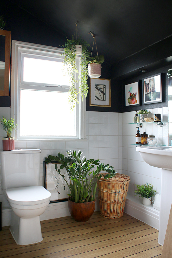 Boho glam black bathroom with plants, wood and gold accents