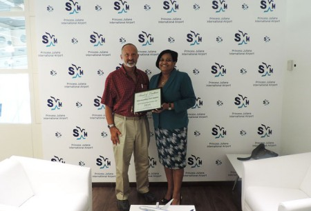 Jeff Berger (L), CEO of JMB Communications, presents the Award of Excellence for SXM to Regina LaBega, Managing Director of SXM Airport in her office last week. (SXM photo)
