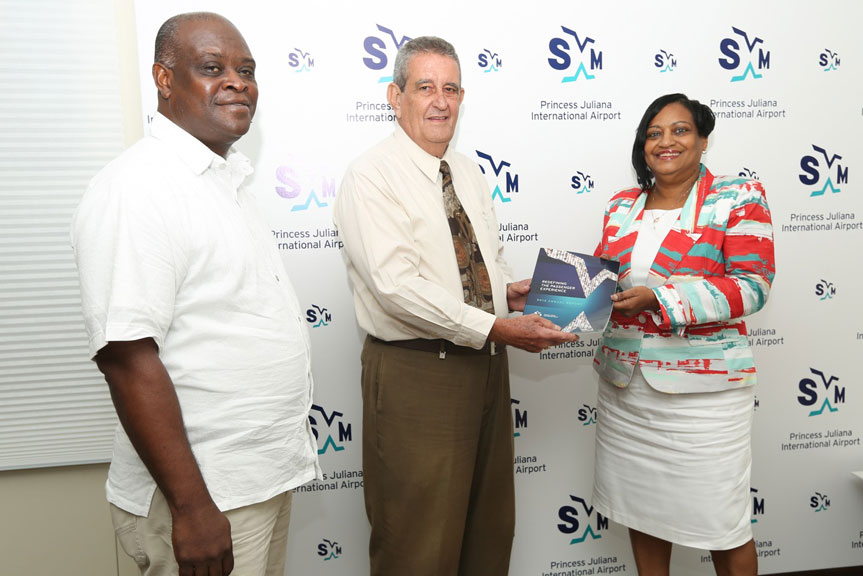 Managing Director of the Holding Company Joe Peterson (center) receives the Annual Report from SXM Managing Director Regina LaBega while Minister Ted Richardson looks on. (SXM photo)
