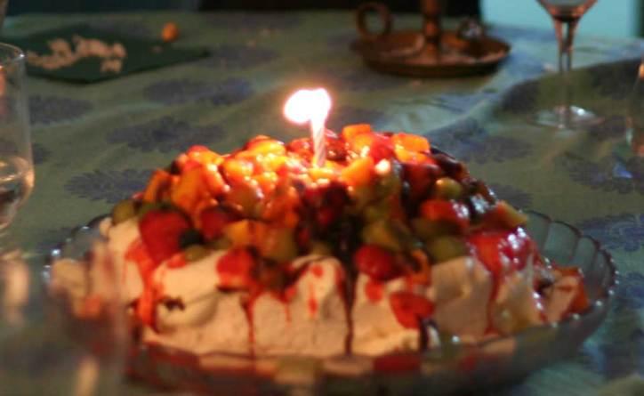 Pavlova birthday cake covered in fruit