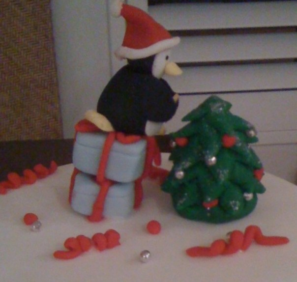 Cake with penguin reaching to put star on Christmas tree