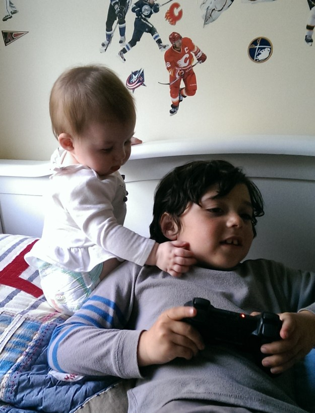 Luc loves to grab Sydney's cheeks, so Sydney does it back to him. Apparently, she is smart enough to get him while he's completely immersed in his video game!