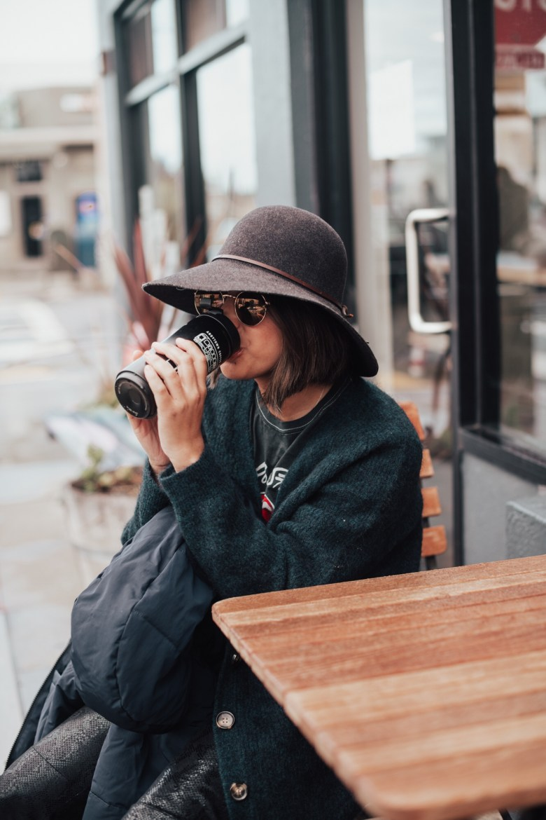 Coffee Gifts by popular San Francisco life and style blog, Sylvie in the Sky: image of a woman wearing a felt hat, baggy black sweater and black pants while sitting outside and drinking out of a black insulated coffee cup.