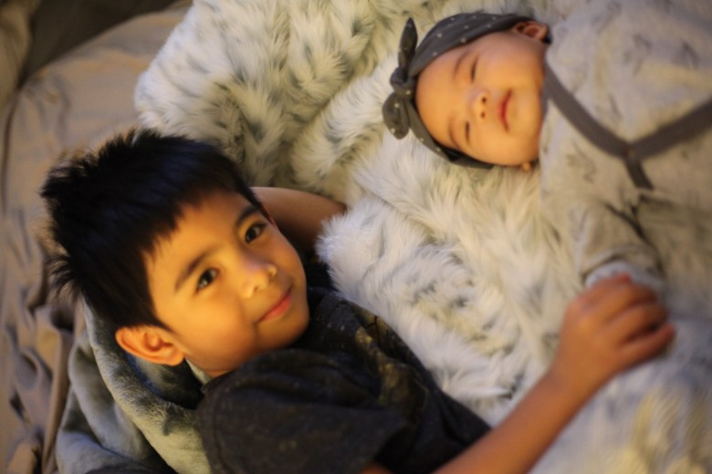 Natural Cold Remedies for Kids featured by top US mom blogger Sylvie in the Sky | Natural Cold Remedies for Kids by popular San Francisco life and style blog, Sylvie in the Sky: image of a young boy and girl laying on a bed together.