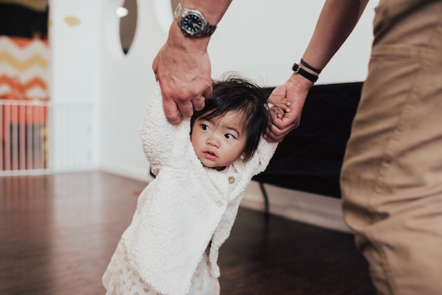 14 Amazing Activities for Dads and Kids by top US lifestyle blog, Sylvie in the Skye: image of man holding baby girl's hands.