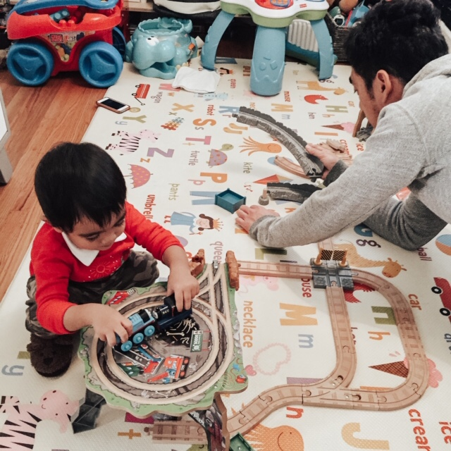 14 Amazing Activities for Dads and Kids by top US lifestyle blog, Sylvie in the Skye: image of a man and a boy playing with Thomas and Friends trains and train tracks on a wood floor.