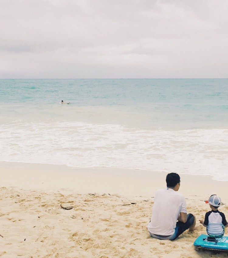 14 Amazing Activities for Dads and Kids by top US lifestyle blog, Sylvie in the Skye: image of man and kid sitting on a surfboard on the sand at the beach.