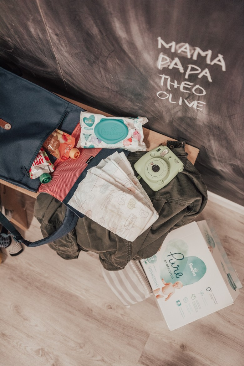 14 Amazing Activities for Dads and Kids by top US lifestyle blog, Sylvie in the Skye: image of chalkboard with family names written on it, polaroid instax camera, Pampers Pure Protection diapers, Pampers diaper wipes, blue diaper bag, applesauce pouches, and green jacket.