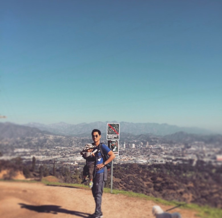 14 Amazing Activities for Dads and Kids by top US lifestyle blog, Sylvie in the Skye: image of man standing on a trail with the view of a city and mountains in the background, and wearing a baby carrier with a baby in it.