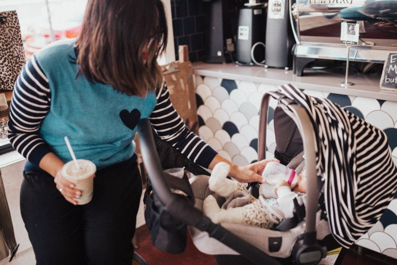 The Best Breastfeeding Essentials by popular California mommy blog, Sylvie in the Sky: image of a woman feeding her baby a bottle in a restaurant.