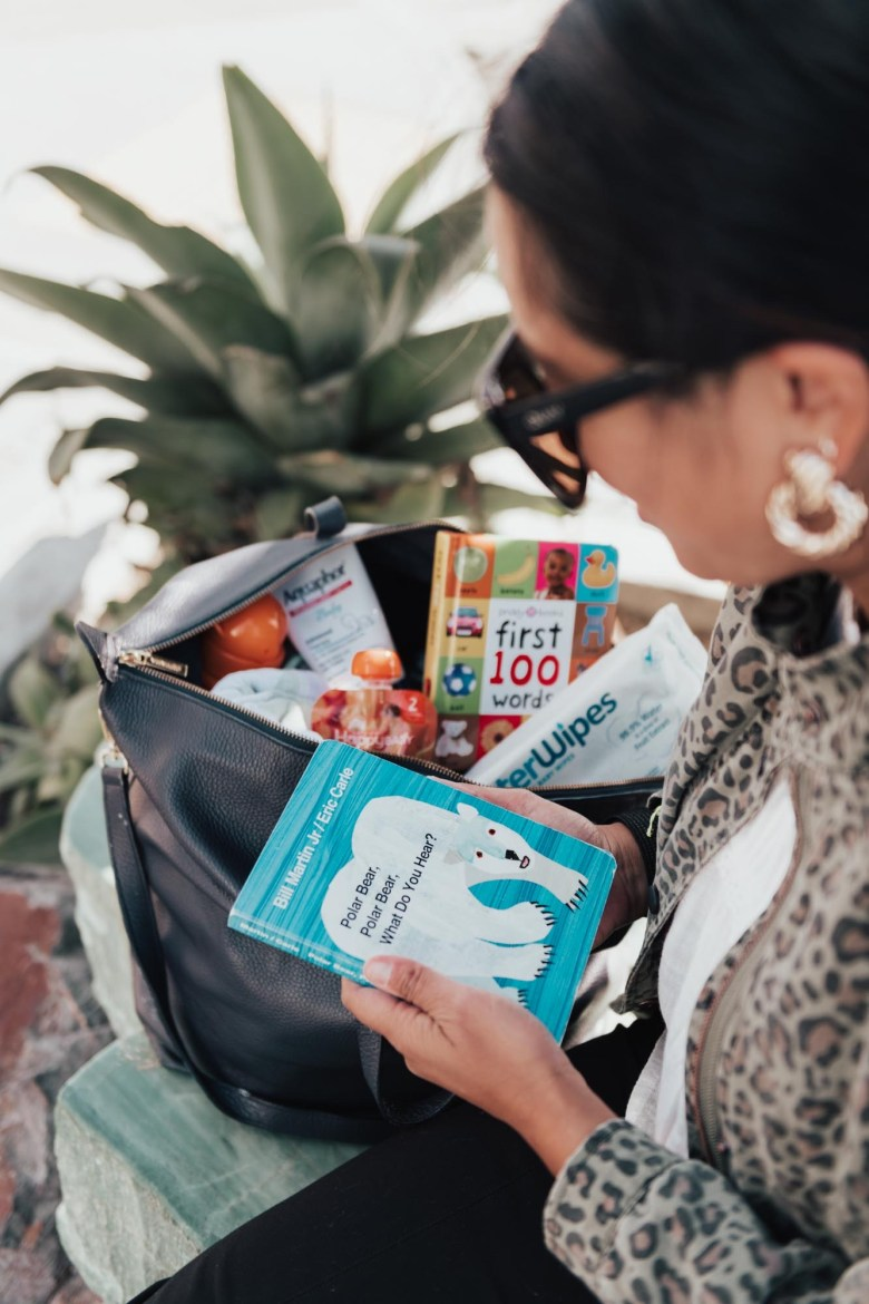 Best Diaper Bag Essentials for 2019 & 2020 by popular San Francisco lifestyle blog, Sylvie in the Sky: image of a woman holding the 'Polar Bear, Polar Bear What do you See' board book and sitting next to an opened diaper bag with books, wipes, diapers, and snacks.