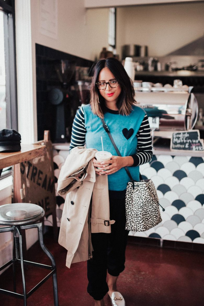 Women's Trench Coats and Outfit Inspiration by popular San Francisco fashion blog, Sylvie in the Sky: image of a woman standing inside a coffee shop and holding a TopShop Staple Trench Coat.