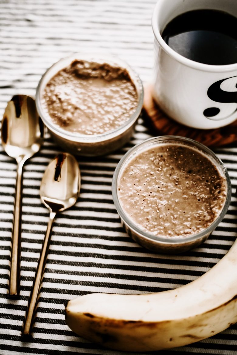 Vegan Chia Pudding Recipe by popular San Francisco lifestyle blog, Sylvie in the Sky: image of two vegan chia pudding cups, two gold spoons, a banana, and a cup of coffee.