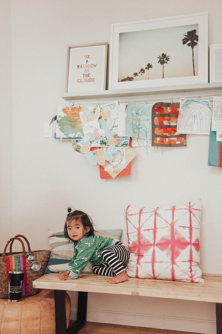 10 Best Baby Proofing Products for Every Home by popular San Francisco mom blog, Sylvie in the Sky: image of a toddler girl sitting on a wood bench.