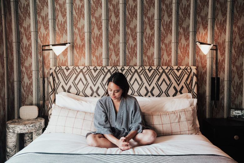 How to Sleep Better by popular San Francisco lifestyle blog, Sylvie in the Sky: image of woman sitting on a bed and meditating.