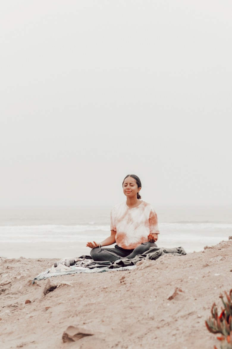 Best Yoga Apps by popular San Francisco lifestyle blog, Sylvie in the Sky: image of a woman meditating at the beach.