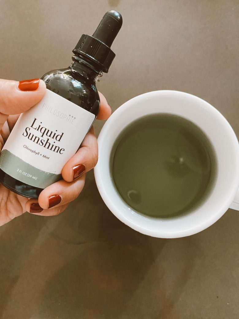 Chlorophyll Water by popular San Francisco lifestyle blog, Sylvie in the Sky: image of a woman holding a bottle of Liquid Sunshine next to a mug filled with Chlorophyll water.