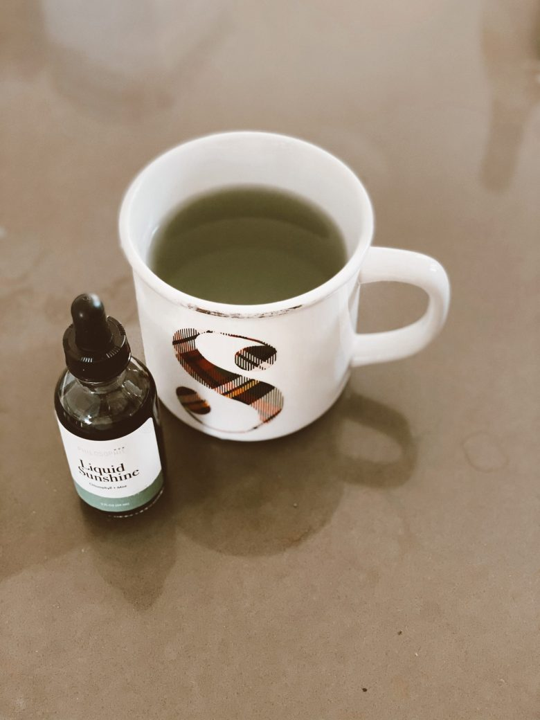 Chlorophyll Water by popular San Francisco lifestyle blog, Sylvie in the Sky: image of a bottle of Liquid Sunshine next to a monogram ceramic mug.