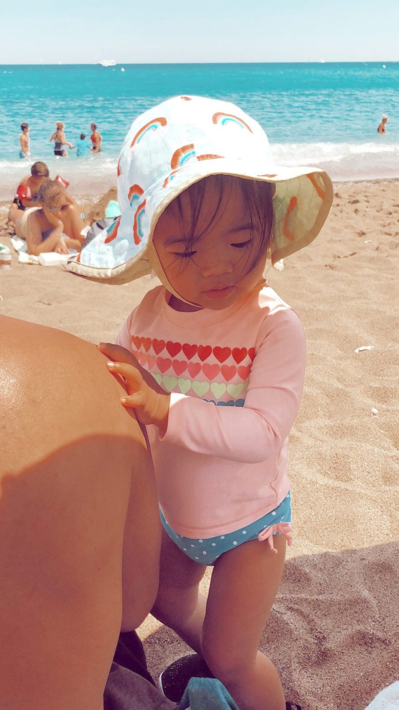 Natural Sunscreen for Babies by popular San Francisco motherhood blog, Sylvie in the Sky: image of a little girl wearing a rainbow sun hat, rainbow heart rash guard and blue and white polka dot swimsuit at the beach.