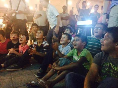 Refugee children watch a showing of Tom and Jerry in Hungary