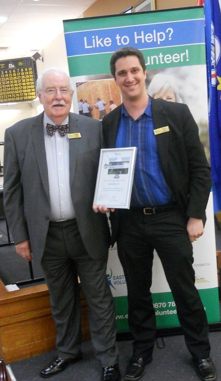 Alex being presented with a certificate for Syneka's $500 donation to the Eastern Volunteers Building Fund