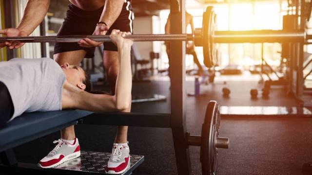 Personal trainer helping woman bench press